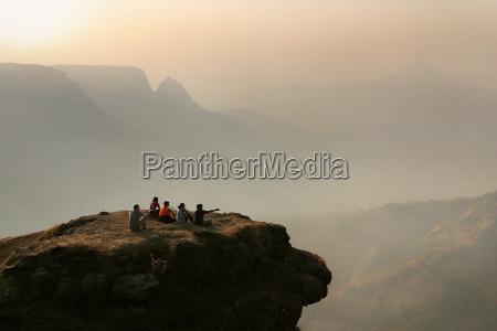 grupa ludzi siedzi przed gorski krajobraz