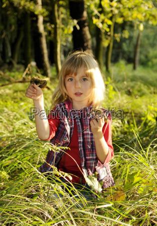 dziewczyna zbiera grzyby w lesie