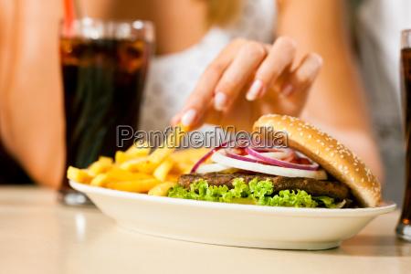 dwie kobiety jedzenie hamburgerow i picia