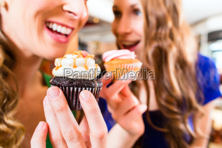 kobiety jedzenia babeczki podczas picia kawy