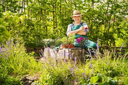 ogrod ogrodnik sadzi slomkowy kapelusz siedzi